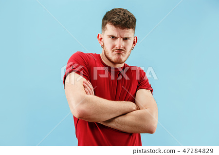 The young emotional sad angry man on blue studio background 47284829