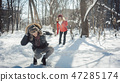 Woman throwing snowball on her guy in winter in playful mood 47285174