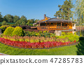 A flowerbed with red flowers and all shades of gre 47285783