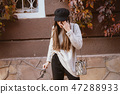 Young woman suffering headache, standing on the street 47288933