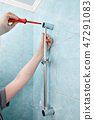 repairman hands mounted on wall holder shower 47291083