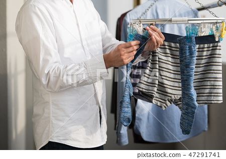 Young Japanese man hanging out laundry on the veranda 47291741