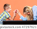 Mother and son arm wrestling. 47297621