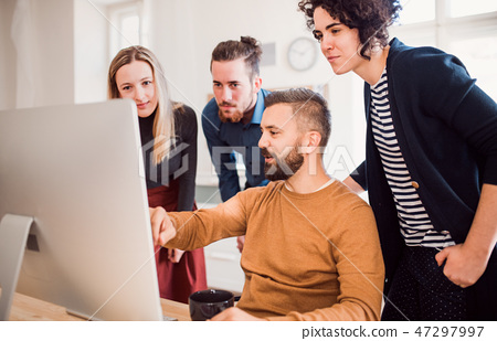 Group of young businesspeople looking at laptop screen in office, discussing issues. 47297997
