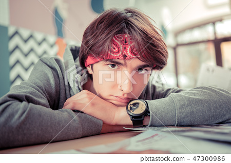 Teenager wearing a bandanna and a watch putting his head on hands 47300986