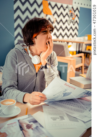 Student yawning while doing a lot of homework 47301019