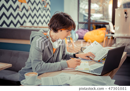 Student concentratedly writing his own research project 47301081