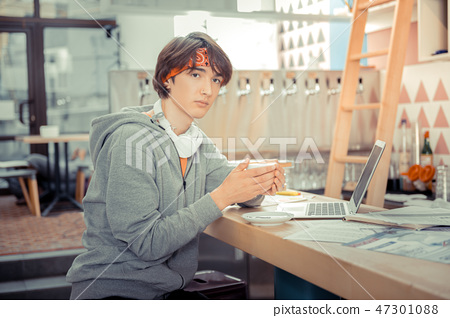 Teenager drinking coffee and working with computer i th cafe 47301088