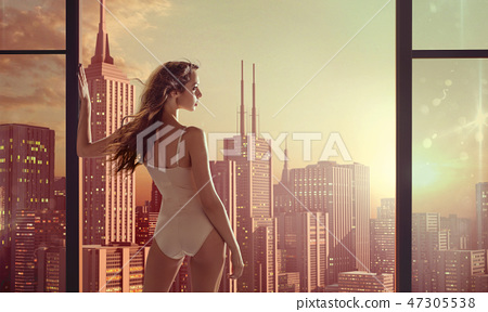 Brunette lady staring at beautiful sunrise 47305538