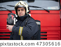 Photo of young man fireman with mask in hands near fire truck 47305616