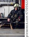 Image of happy fireman in helmet with dog 47305622