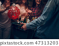 Man holding box with bottles of champagne at a party 47313203