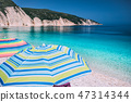 Tranquil beach scene. Picturesque landscape of mediterranean island with colorful umbrellas. Summer 47314344