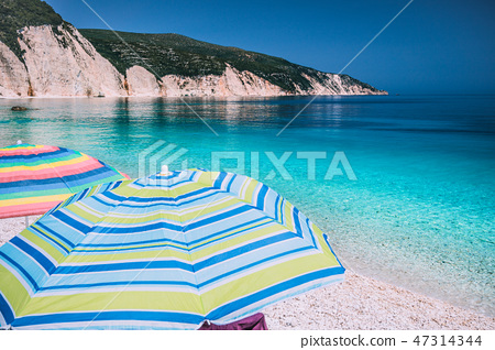 Tranquil beach scene. Picturesque landscape of mediterranean island with colorful umbrellas. Summer 47314344