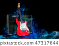 Electric guitar and amplifier surrounded by smoke 47317644