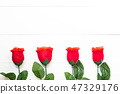 Present gift with red rose flower on wooden table 47329176