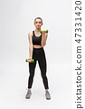 Portrait of Caucasian woman on white background wearing black fitness separate and excercising with 47331420