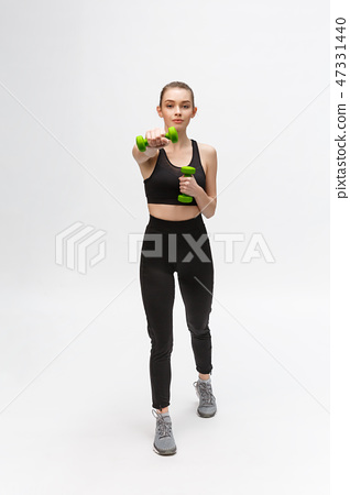 Portrait of Caucasian woman on white background wearing black fitness separate and excercising with 47331440