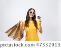 Close-up portrait of happy young brunette woman in sunglasses holding credit card and colorful 47332913
