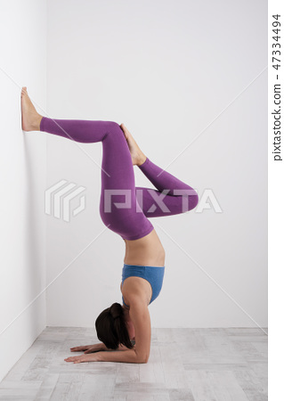Young brunette woman in purple leggings and a sports t-shirt does exercises on the floor. Balances 47334494
