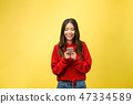 Young beautiful happy woman using smart phone. Isolated on yellow background 47334589