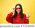 Pretty happy woman in red sunglasses over colorful background 47334685