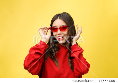 Pretty happy woman in red sunglasses over colorful background 47334686