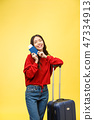 Woman travel. Young beautiful asian woman traveler with suitcase and passport on yellow background 47334913