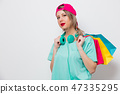 girl in pink cap and blue t-shirt with shopping bags 47335295