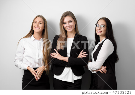Three beautiful young smiling woman in business clothes on a white background. 47335525