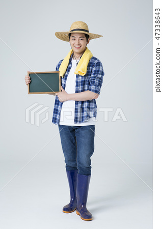 Agriculture industry, farming and people concept. Young farmer gesturing over gray background. 002 47338643