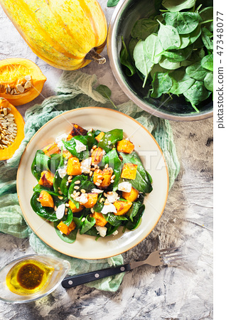 Roasted pumpkin salad with spinach and nuts 47348077
