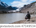 Man by lake looking at Alpine glacier 47349534