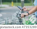 Renting bicycle from urban bicycle sharing station 47353289
