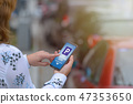 Woman using smartphone app to pay for parking 47353650