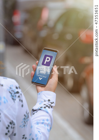 Woman using smartphone app to pay for parking 47353651