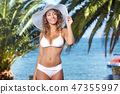 Pretty young woman holding her hat on her head, at the beach 47355997