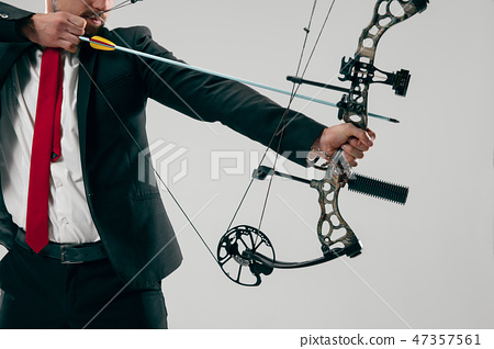 Businessman aiming at target with bow and arrow, isolated on white background 47357561