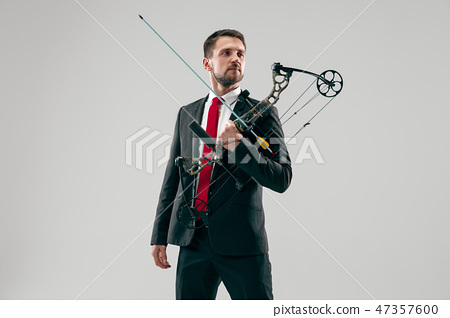 Businessman aiming at target with bow and arrow, isolated on white background 47357600