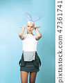 young pretty blond girl with rabbit ears posing cheerful on blue background, lifestyle people 47361741