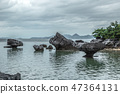 Rocky stones are standing in the sea shallows at cloudy day 47364131
