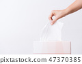 Woman hand picking white tissue paper from box 47370385