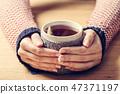 Hot mug of tea warming woman's hands in retro jumper. 47371197