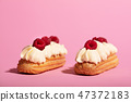 Two colorful eclairs laying on pink background. 47372183