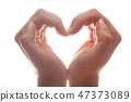 Woman's hands make a heart shape on white background, backlight. Love 47373089