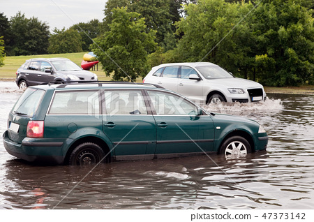 Cars trying to drive against flood on the street in Gdansk, Poland. 47373142