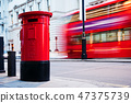 Traditional red mail letter box and red bus in motion in London, the UK. 47375739