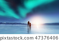 Adventurous man standing with a backpack, looking at aurora. 47376406