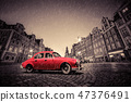 Retro red car on cobblestone historic old town in rain. Wroclaw, Poland. 47376491