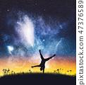 Acrobat man standing on one hand on night sky. 47376589